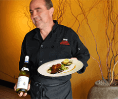 Chef Gorji carrying plate and wine at mediterranean fine dining Dallas Gorji Restaurant.