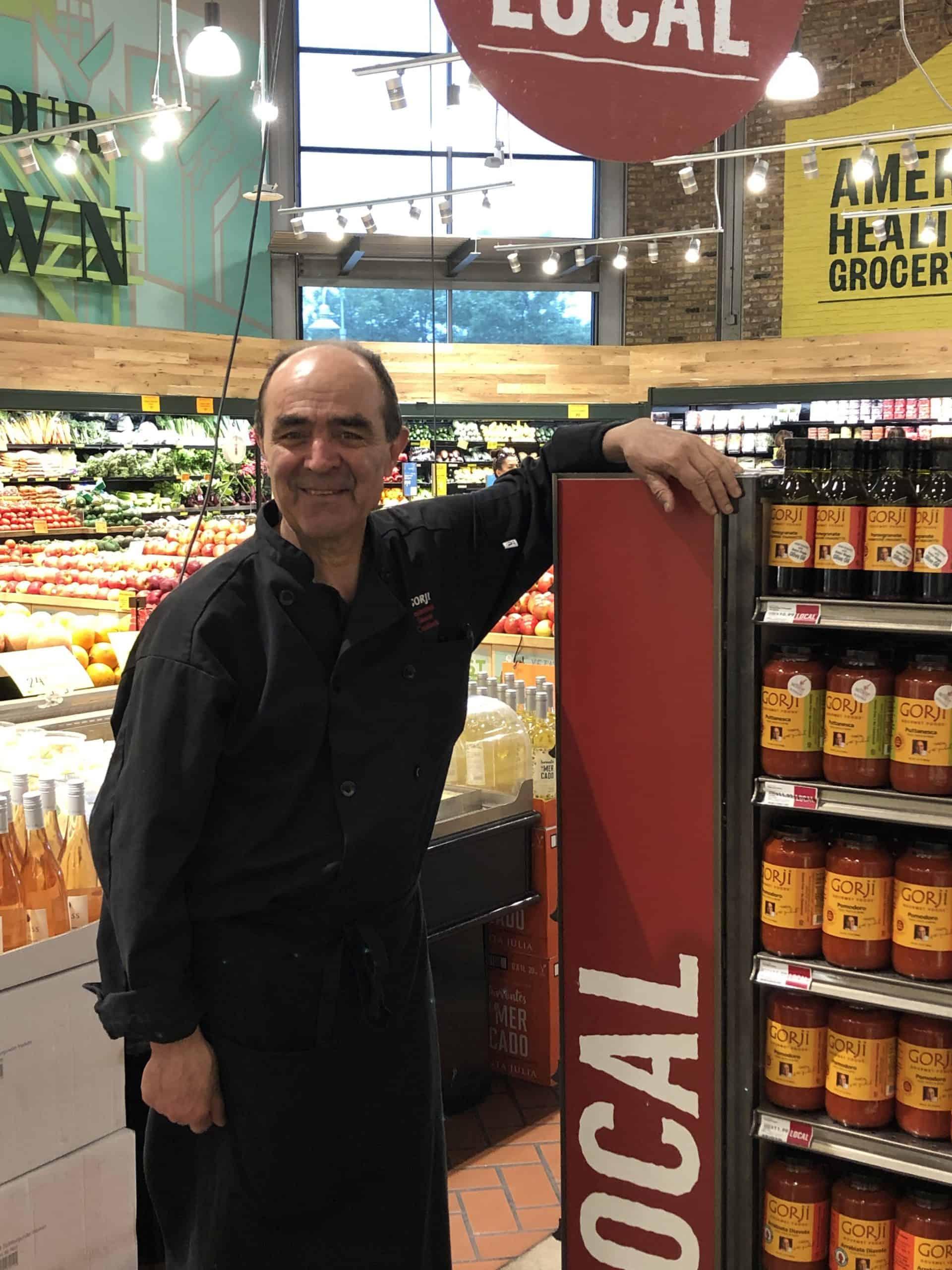 Chef Gorji standing by mobile display of Gorji Gourmet sauces.